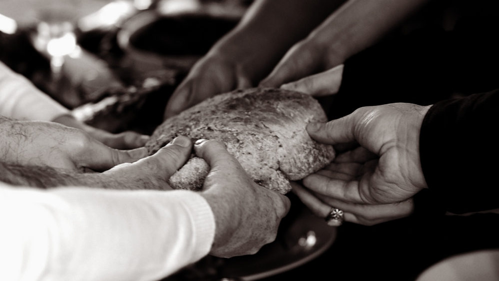 hands breaking bread